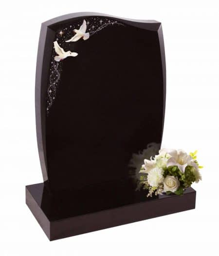 Black headstone with white flying birds