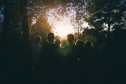 A family of mourners watching the sun set through the trees