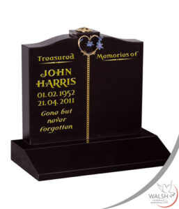 Memorial headstone with gold heart, flowers and inscription